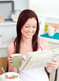 Glückliche Frau, die Getreide beim Lesen der Zeitung isst Stockfoto