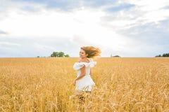 Glückliche Frau, die in goldenen Weizen springt lizenzfreie stockfotos