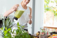 Glückliche Frau, die grünes Cocktail gießt lizenzfreie stockfotografie