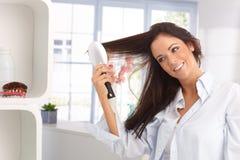 Glückliche Frau, die Haar kämmt Stockfotografie