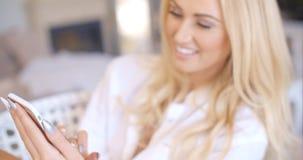 Glückliche Frau, die an Hand ihr Telefon betrachtet Stockbilder