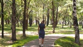 Glückliche Frau, die am Handy, draußen spricht Mädchen, das am Telefon geht in den Park spricht Attraktive junge Frau stock footage