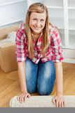 Glückliche Frau, die heraus einen Teppich rollt Lizenzfreie Stockfotos