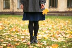 Glückliche Frau, die in Herbststadtpark geht Regnerisches Wetter und gelbe Bäume herum stockfotografie