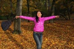 Glückliche Frau, die am Herbsttag im Park genießt Stockbild