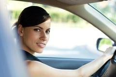 Glückliche Frau, die ihr Auto antreibt Stockbild