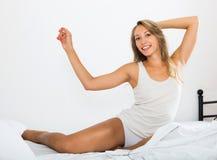 Glückliche Frau, die in ihrem Schlafzimmer lächelt stockbild