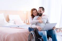 Glückliche Frau, die ihren behinderten Mann umarmt Lizenzfreie Stockbilder