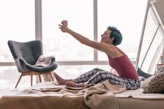 Glückliche Frau, die ihren Körper beim morgens aufwachen ausdehnt lizenzfreies stockfoto
