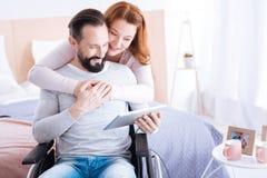 Glückliche Frau, die ihren verkrüppelten Mann umarmt Stockbilder