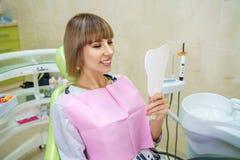 Glückliche Frau, die im Büro des Zahnarztes, gesunde Zähne sitzt stockbild