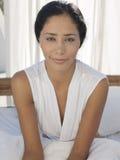 Glückliche Frau, die im Bett sitzt Stockfoto