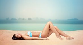 Glückliche Frau, die im Bikini über Swimmingpool sich bräunt Stockbild