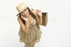 Glückliche Frau, die im Einkaufszentrum spricht am Telefon steht Stockfotografie