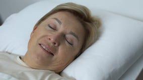 Glückliche Frau, die im Krankenhausbett nach Chirurgieoperation, Wiederaufnahme, Gesundheit liegt stock footage