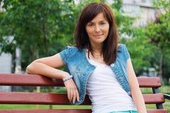 Glückliche Frau, die im Park sich entspannt Schöne junge Frau draußen Genießen Sie Natur Gesundes lächelndes Mädchen auf Hintergr Lizenzfreie Stockfotografie