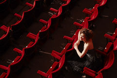 Glückliche Frau, die im Theater-Stall sitzt lizenzfreies stockbild