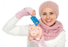 Glückliche Frau, die Kreditkarte in piggy Querneigung einsetzt lizenzfreies stockfoto