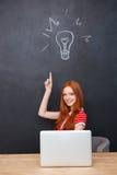 Glückliche Frau, die Laptop und pointin oben über Tafelhintergrund verwendet stockfoto
