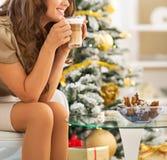 Glückliche Frau, die Latte macchiato nahe Weihnachtsbaum genießt stockfotografie