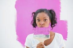 Glückliche Frau, die lustiges Gesicht hinter Malerpinsel macht Lizenzfreies Stockfoto