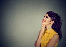 Glückliche Frau, die mit der Hand auf dem Kinn oben schaut denkt Lizenzfreie Stockfotos