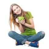 Glückliche Frau, die mit der Kaffeetasse lokalisiert auf Weiß sitzt Stockfotos