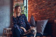 Glückliche Frau, die mit einem netten Pug in einem Raum mit Dachbodeninnenraum sitzt Stockfotografie