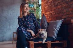 Glückliche Frau, die mit einem netten Pug in einem Raum mit Dachbodeninnenraum sitzt Lizenzfreie Stockbilder