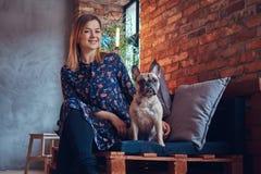 Glückliche Frau, die mit einem netten Pug in einem Raum mit Dachbodeninnenraum sitzt Lizenzfreie Stockfotografie