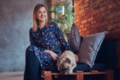 Glückliche Frau, die mit einem netten Pug in einem Raum mit Dachbodeninnenraum sitzt Lizenzfreies Stockbild