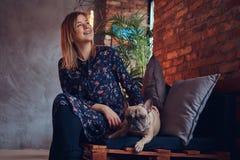Glückliche Frau, die mit einem netten Pug in einem Raum mit Dachbodeninnenraum sitzt Stockfotos