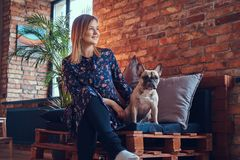 Glückliche Frau, die mit einem netten Pug in einem Raum mit Dachbodeninnenraum sitzt Stockbilder