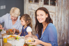 Glückliche Frau, die mit Familie frühstückt stockbild