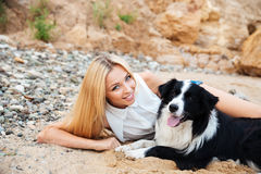 Glückliche Frau, die mit Hund auf dem Strand liegt Lizenzfreies Stockbild