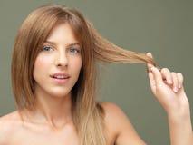 Glückliche Frau, die mit ihrem Haar spielt lizenzfreie stockbilder