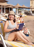 Glückliche Frau, die mit Laptop am Strand sitzt Stockbild