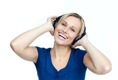 Glückliche Frau, die Musik auf Kopfhörern hört Stockbild