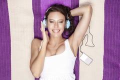 Glückliche Frau, die Musik durch MP3-Player unter Verwendung der Kopfhörer beim Lügen auf Picknickdecke hört Stockbild