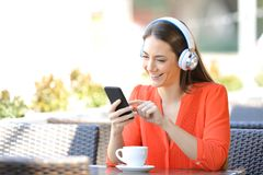 Gl?ckliche Frau, die Musik in einer Kaffeestube h?rt stockfoto