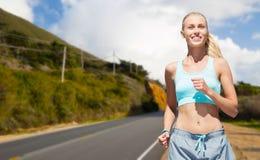 Glückliche Frau, die nahe gelegene Straße über Big- Surhügeln laufen lässt Lizenzfreies Stockfoto