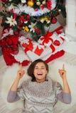 Glückliche Frau, die nahe Weihnachtsbaum legt Lizenzfreie Stockbilder