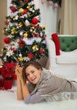 Glückliche Frau, die nahe Weihnachtsbaum legt Stockfoto