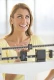 Glückliche Frau, die oben bei der Anwendung der Ausgleichsgewicht-Skala schaut Stockfoto