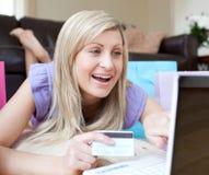 Glückliche Frau, die online kauft, liegend auf dem Fußboden Stockfotografie