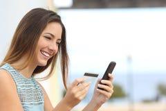 Glückliche Frau, die online mit einem intelligenten Telefon kauft Stockbild