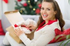Glückliche Frau, die Paket mit Weihnachtsgeschenk entpackt Stockfoto