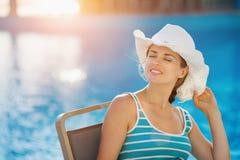 Glückliche Frau, die am Poolstab sitzt Stockfoto