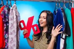 Glückliche Frau, die Prozent-Zeichen am Kleidungs-Gestell mit Kleid hält Stockfotos