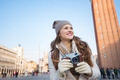 Glückliche Frau, die Retro- Fotokamera auf Marktplatz San Marco hält Lizenzfreie Stockfotos